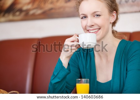 Portrait of happy female customer having coffee in cafe