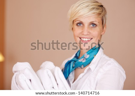 Portrait of happy female housekeeper with bathrobes