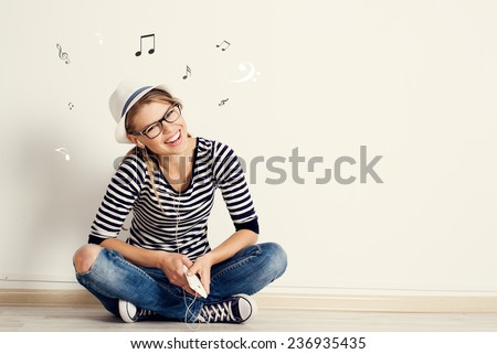 Portrait of happy female listening musical composition in earphones with sheet music and clef drawn on the wall. Young pretty Caucasian woman sitting on wooden floor in her house.  #236935435