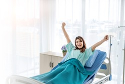 Portrait of happy female patient in hospital room with cheerful posture. The sick inpatient smiling to her doctor and nurse as she recovering and worry free. Insurance concept. Copy space provided.