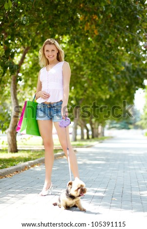 Portrait of happy female strolling with fluffy pet in park