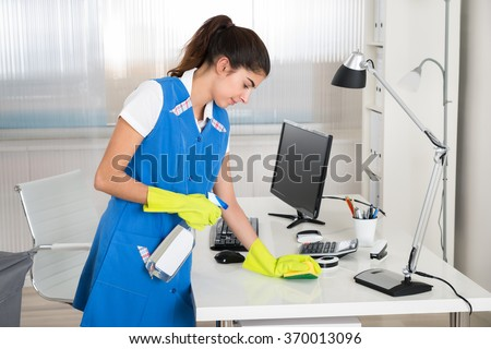 Portrait of happy female worker cleaning computer desk with spray and sponge at office
