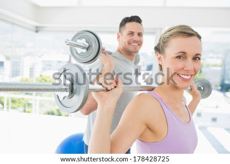 Portrait of happy fit woman and man lifting barbells in the gym