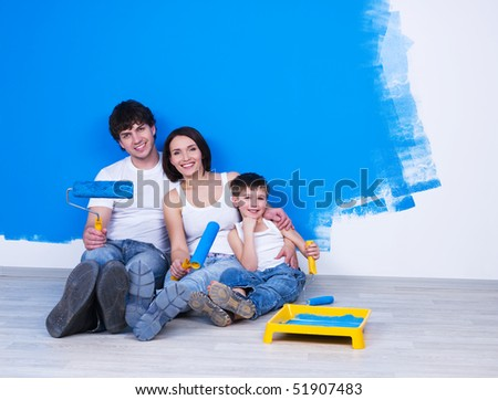 Portrait of happy friendly family sitting on the floor with paintbrush