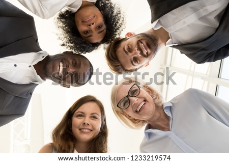 Portrait of happy friendly multi-ethnic team business people faces looking at camera, smiling diverse workers employees group gather in circle together, unity teambuilding concept, below bottom view