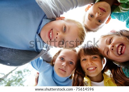 Portrait of happy friends looking at camera with cute boy in front