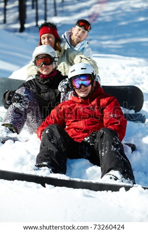 Portrait of happy friends snowboarding during winter vacations