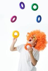 Portrait of happy funny clown kid juggler