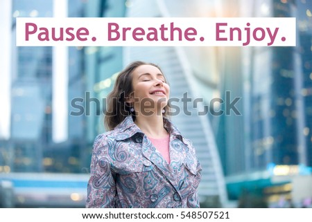Photo of Portrait of happy girl at street, her eyes closed with enjoyment, breathing at full outside. Lady feeling free, successful, ready to start day. Photo with motivational text