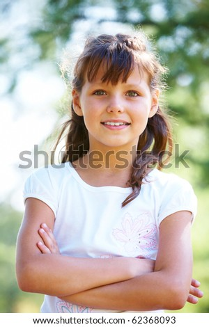 Portrait of happy girl crossing arms while posing outside