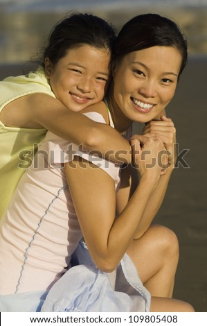 Portrait of happy girl embracing mother on beach
