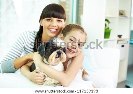 Portrait of happy girl, her mother and their cute pet at home