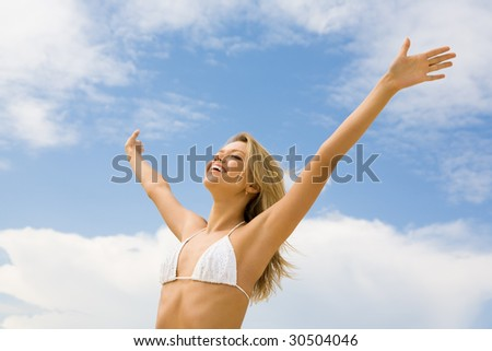 Portrait of happy girl in white bikini praising God with her eyes shut and raised arms on background of cloudy sky