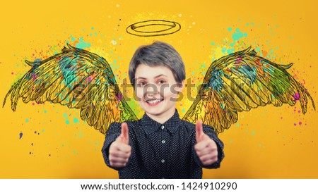 Portrait of happy girl keeps thumbs up over yellow background, smiling broadly imagining herself an angel with fluffy wings behind back and a halo above head. Super power, inner strength concept. #1424910290
