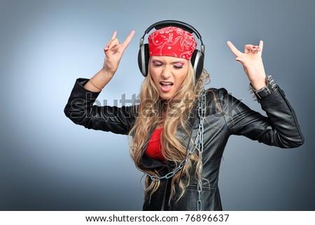 Portrait of happy girl listening a music in headphones. Studio shot over grey background.