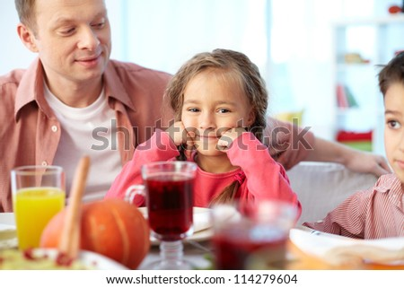 Portrait of happy girl sitting at festive table and looking at camera with her father and brother near by