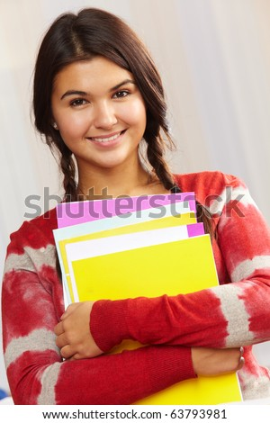 Portrait of happy girl with books looking at camera
