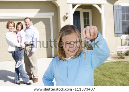 Portrait of happy girl with family holding key in front of new house