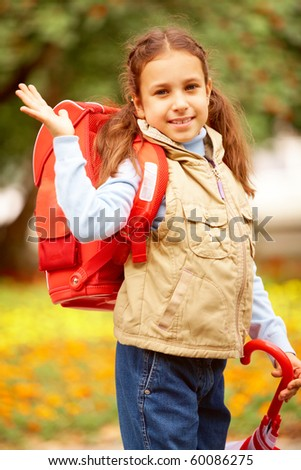 Portrait of happy girl with folded umbrella looking at camera on her way to school