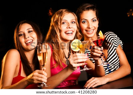 Portrait of happy girlfriends holding martini glasses with cocktails