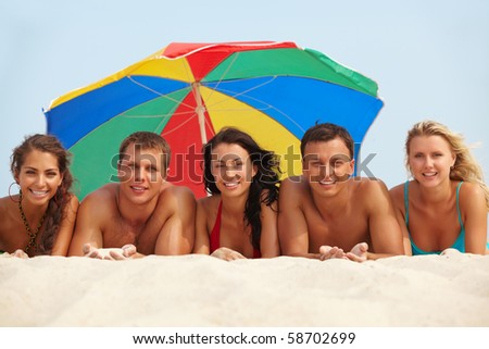 Portrait of happy girls and guys lying on sand on summer vacation