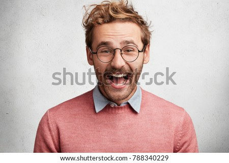 Portrait of happy glad young bearded male with excited cheerful expression, smiles joyfully, being in good mood as recieves good present from someone, isolated over white concrete background. #788340229