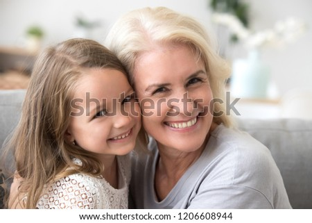 Portrait of happy grandmother and granddaughter spend time at home together, hugging and cuddling on couch, smiling granny embrace cute little grandchild looking at camera making family picture