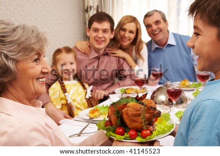 Portrait of happy grandmother holding tray with roasted turkey and looking at her grandson