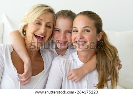 Portrait of happy grandmother, mother and daughter in a white atmosphere. #264175223