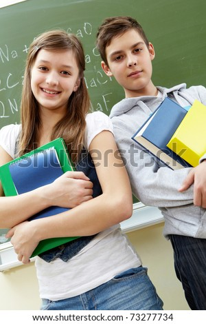 Portrait of happy guy and girl with books looking at camera