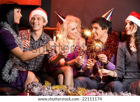 Portrait of happy guys and girls enjoying New Year party with champagne and Bengal lights