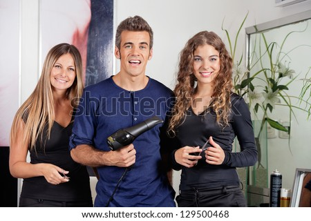 Portrait of happy hairstyling team with dryer and scissors standing together at beauty parlor