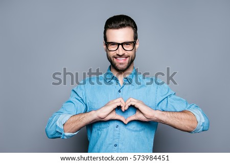 Portrait of happy handsome man in glasses making heart with fingers. #573984451