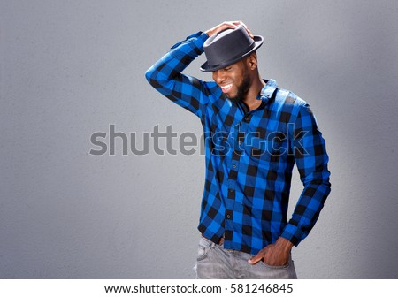 Portrait of happy handsome man laughing with hand to hat #581246845