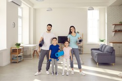 Portrait of happy healthy young family with children standing together in studio apartment, holding sports exercise mats and dumbbells, smiling and looking at camera. Active workout at home concept