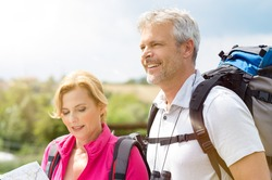 Portrait Of Happy Hikers Analyze The Map In Footpath