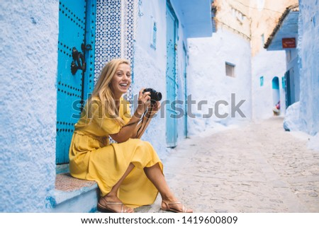 Portrait of happy hipster girl with vintage camera in hands resting in ancient city Morocco enjoying time for photographing beautiful medina buildings, positive woman using retro equipment during trip