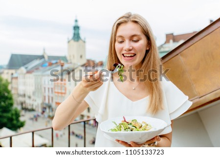 Portrait of happy hungry blond smiling woman holding a bowl with delicious fresh salad and enjoying the european city view on background. Relaxing, tourism, food and resting concept.