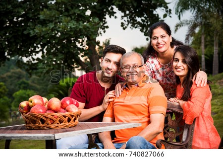 Portrait of Happy Indian/Asian Family while sitting on Lawn chair, outdoor