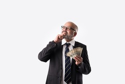 Portrait of happy Indian asian senior businessman holding indian currency notes of five hundred denominations