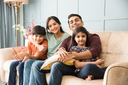Portrait of happy Indian Asian young family while sitting on sofa, lying on floor or sitting against wall