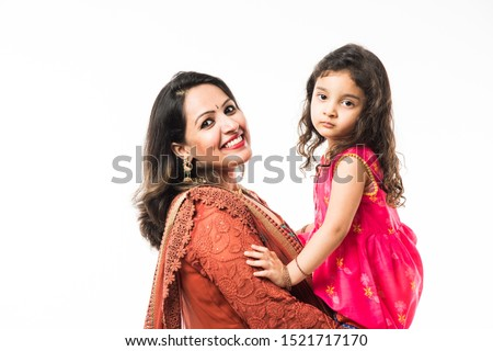 Portrait of Happy Indian mother hugging her daughter in traditional ethnic clothes on some festival day, standing isolated over white background