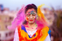 Portrait of happy Indian woman celebrating Holi with powder colours or gulal. Concept of Indian festival Holi.