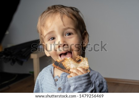 Portrait of happy joyful beautiful little boy eats a delicious pizza. Happiness and joy in his eyes. Super cute small boy.