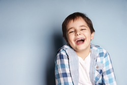 Portrait of happy joyful laughing beautiful little boy on blue background