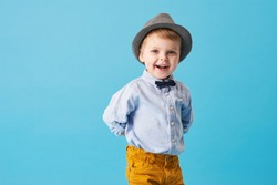 Portrait of happy joyful  little boy isolated on blue background. Toddler child in hat and fashionable suit smiling and have a fun