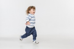 Portrait of happy joyful running beautiful little boy, studio shot on white