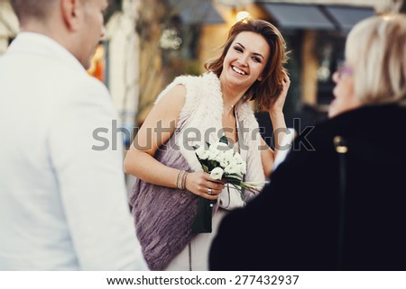 Portrait of happy joyful stylish bride with a bouquet of flowers roses in hand with bracelets and ring