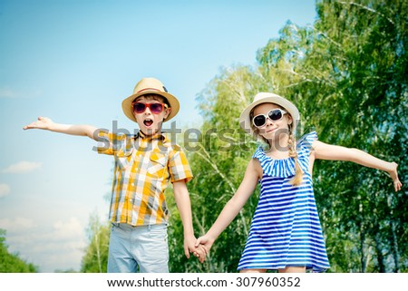 Portrait of happy kids on a bright sunny day. Friendship. Summer holidays.