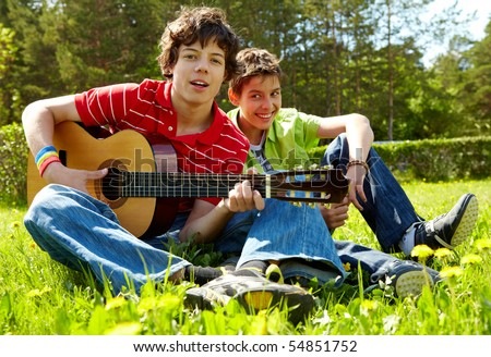 Portrait of happy lad playing the guitar with his friend laughing near by